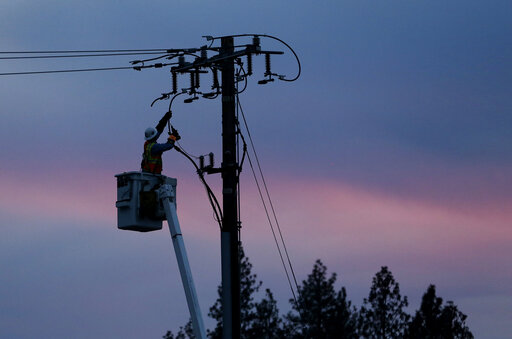 FILE - In this Nov. 26, 2018, file photo, A PG&E lineman works to repair a power line in fire-ravaged Paradise, California on November 26, 2018. (AP Photo/Rich Pedroncelli, File)