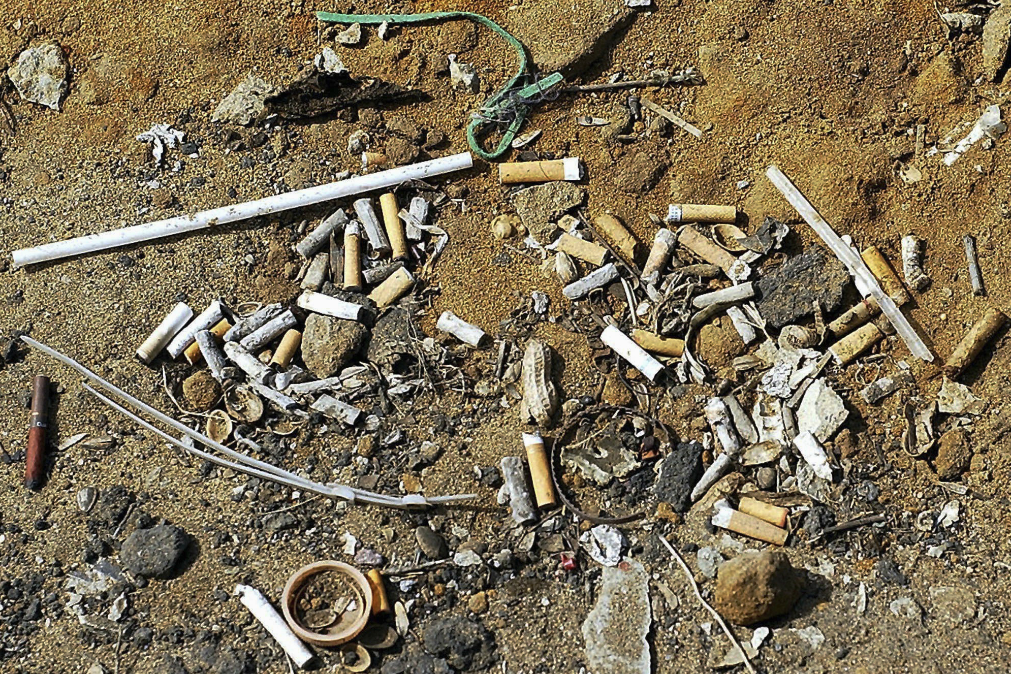 Cigarette butts and plastic polluting a beach