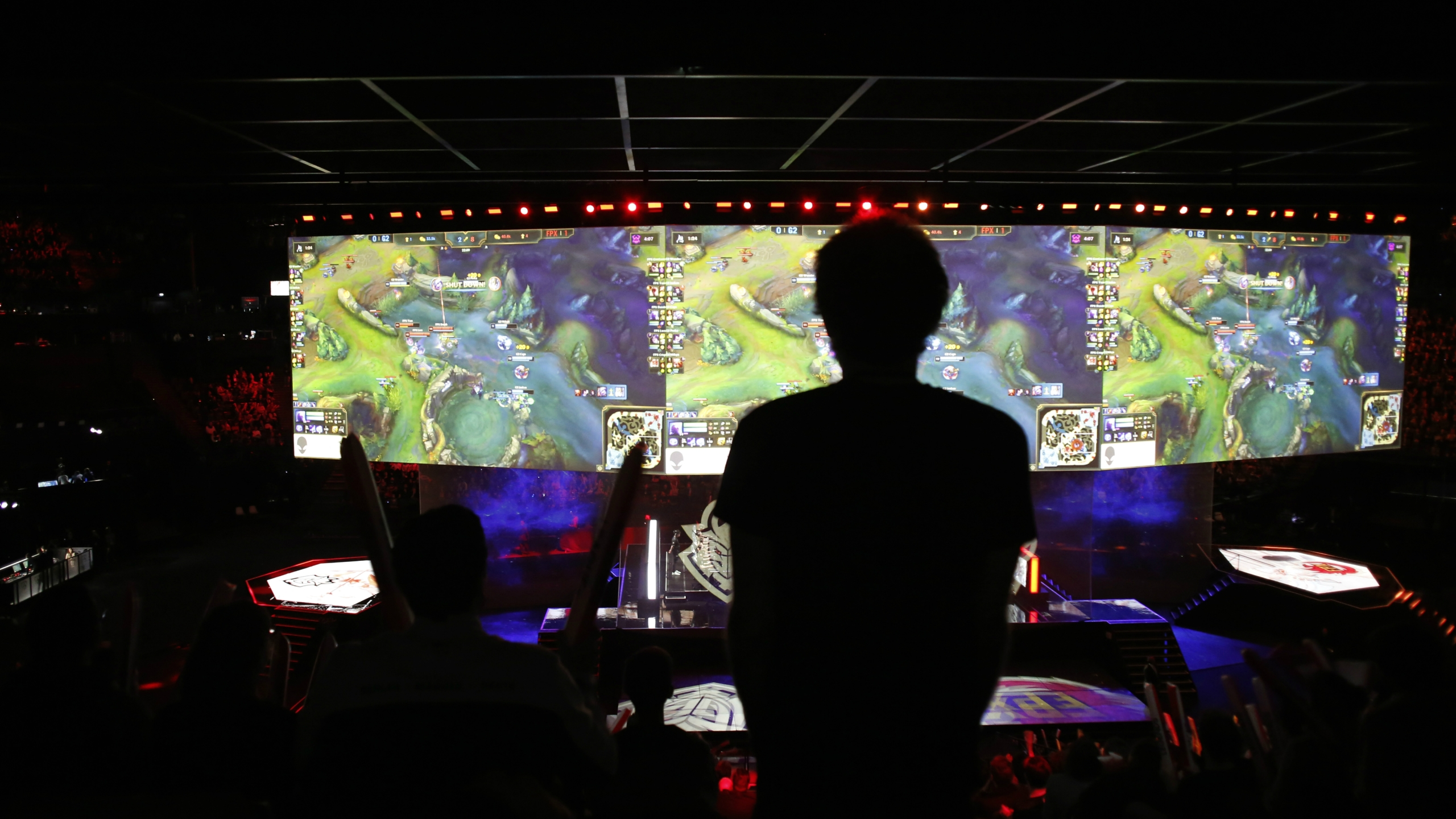 A silhouette outlined against huge screens displaying a League of Legends tournament