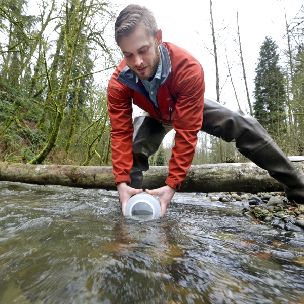 Student takes a water sample from a stream