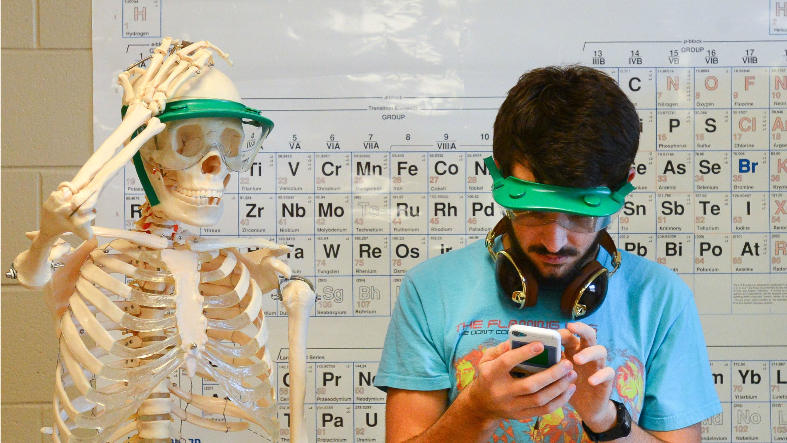 AP student checks phone beside a skeleton and periodic table