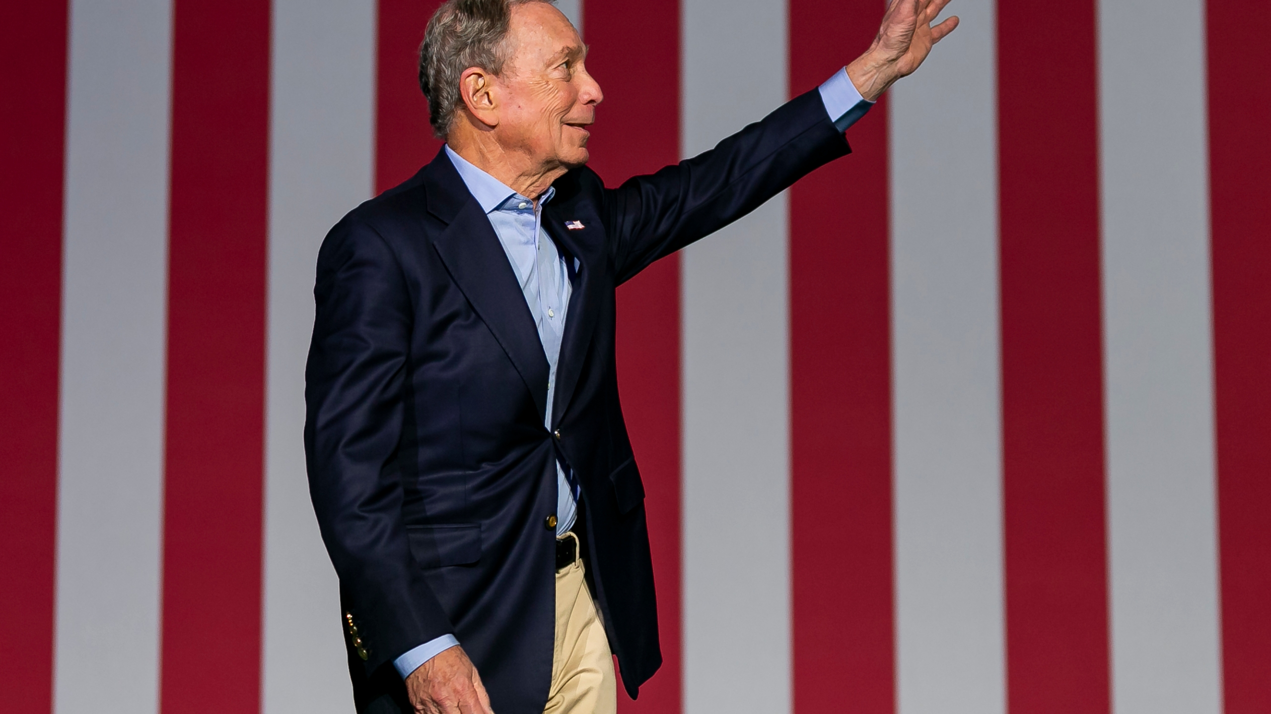 Bloomberg waving in front of American flag