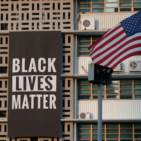 Black Lives Matter sign next to an American Flag