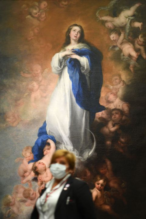 "A woman wearing a face mask stands in front of the painting ""The immaculate Conception of Los venerables"""