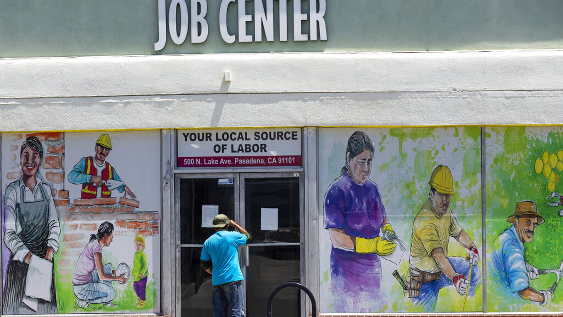 A man peers into a shuttered employment center