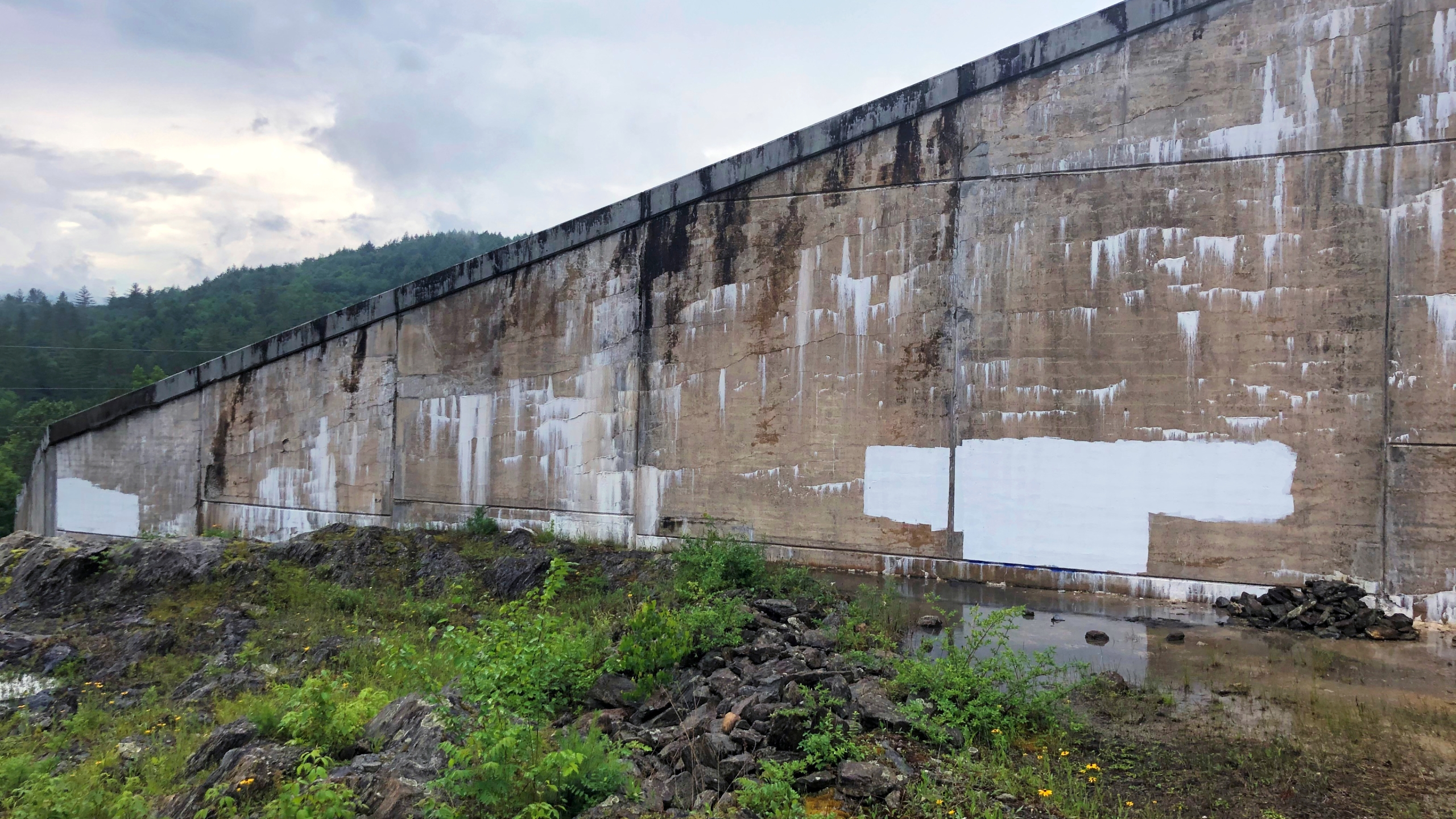 East side of the Waterbury Dam with white paint covering white supremacist graffiti.