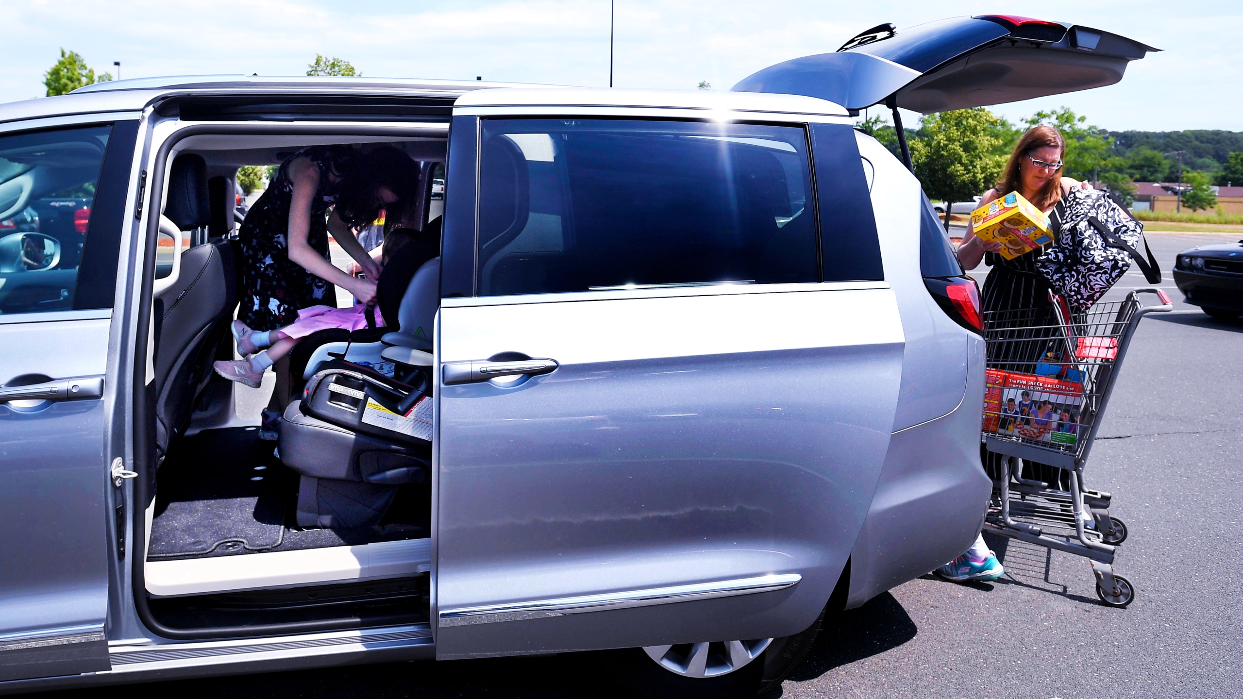 Buckling a child into a car seat in a minivan