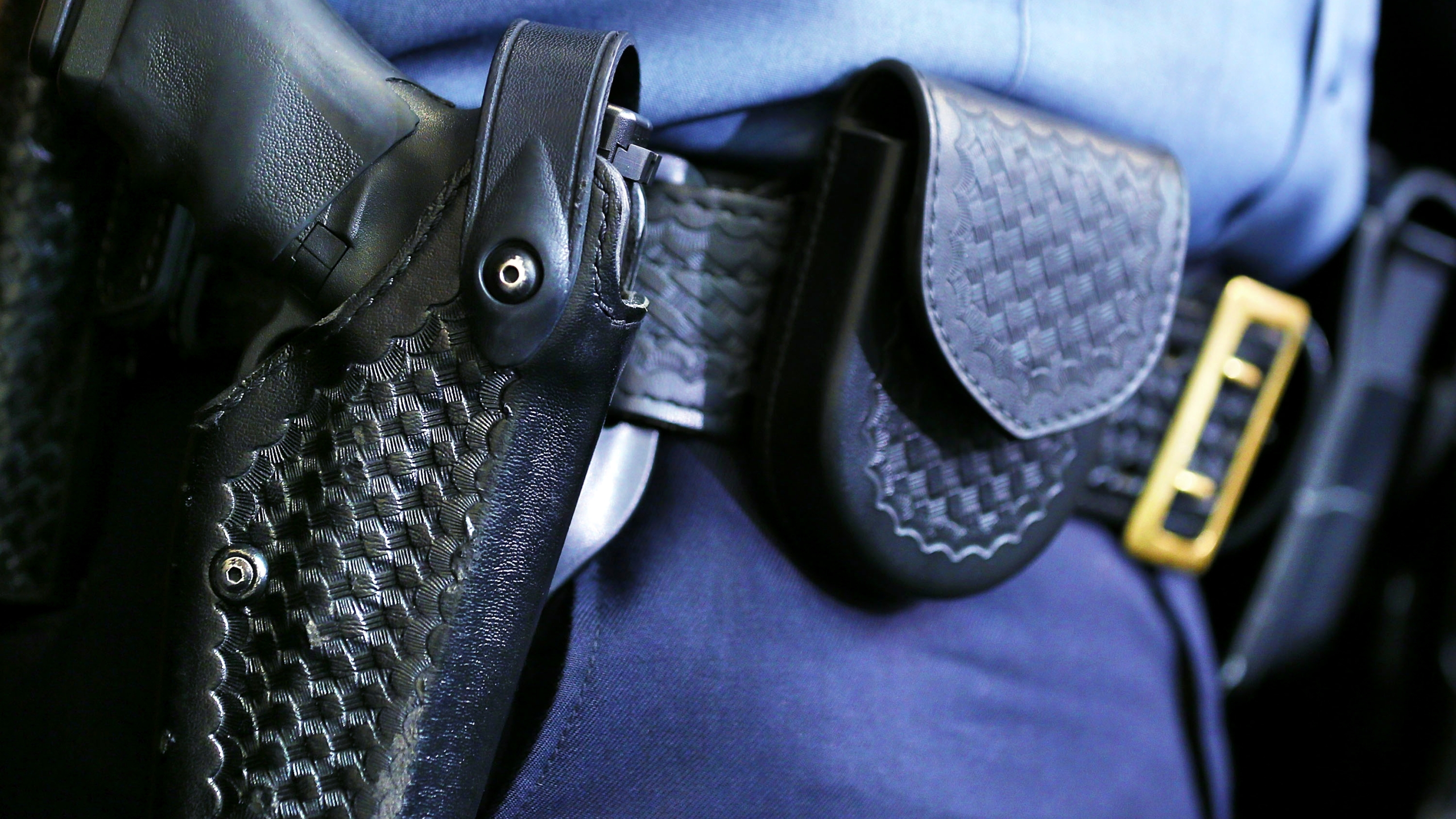 A holstered police gun on an officer's belt