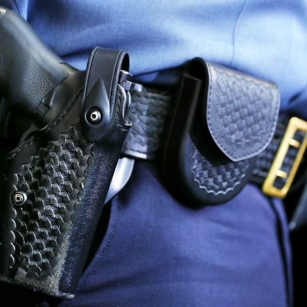 A holstered police gun on an officer's belt