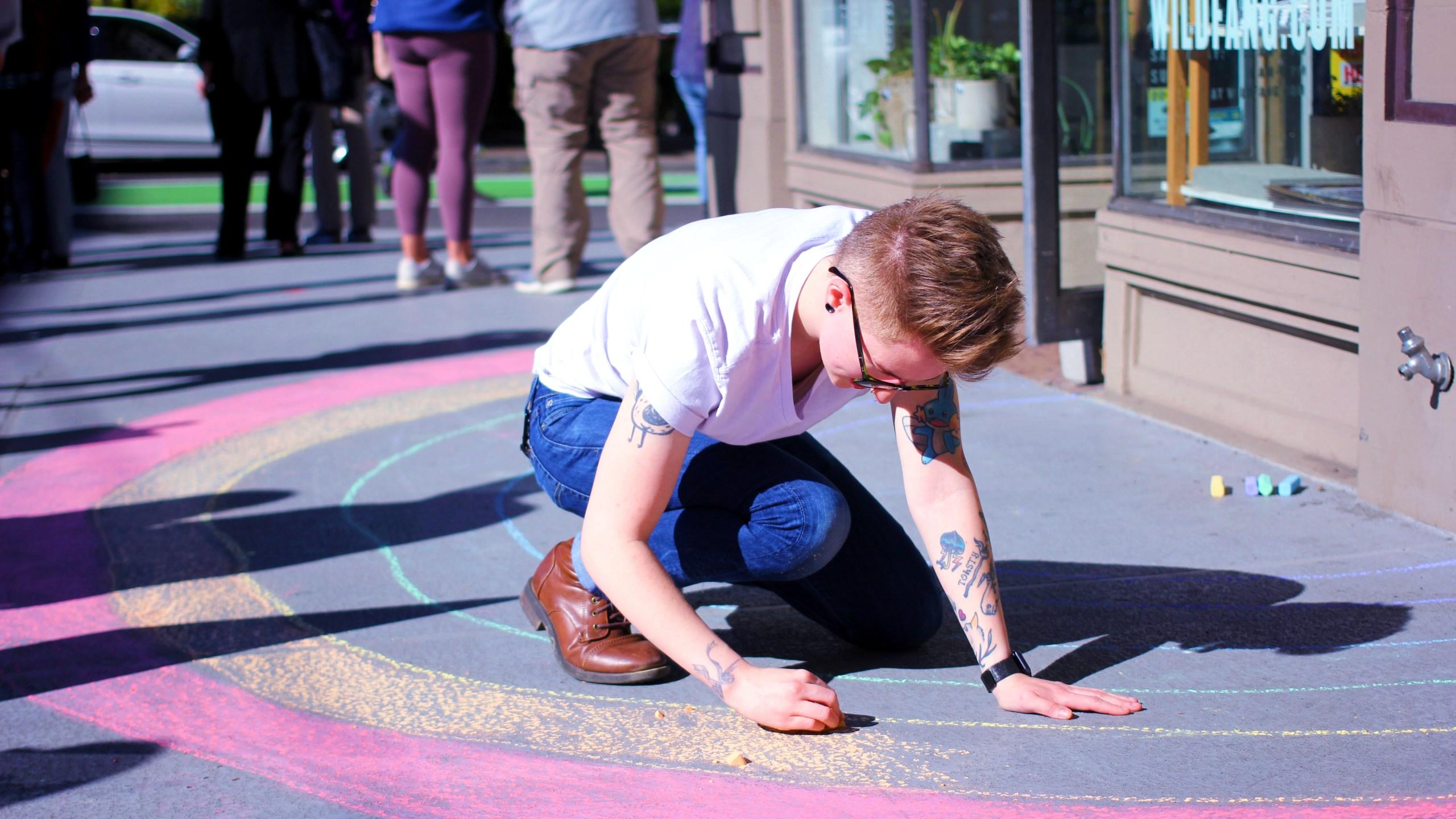 chalk artists draws rainbow on sidewalk
