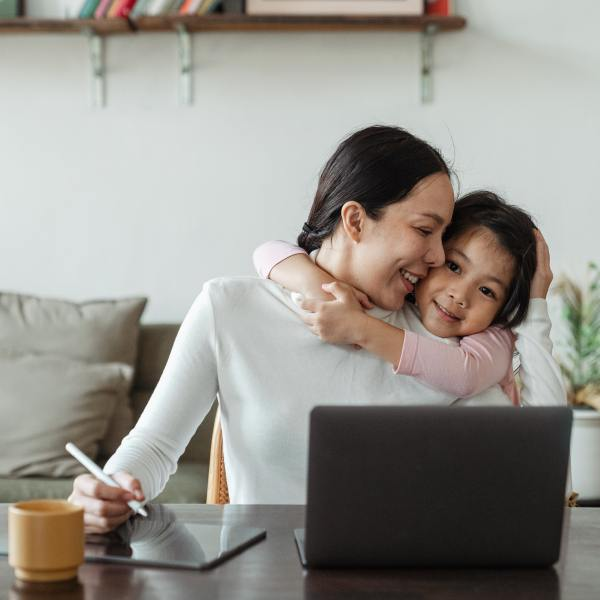 Mom on a laptop distracted by hugging child