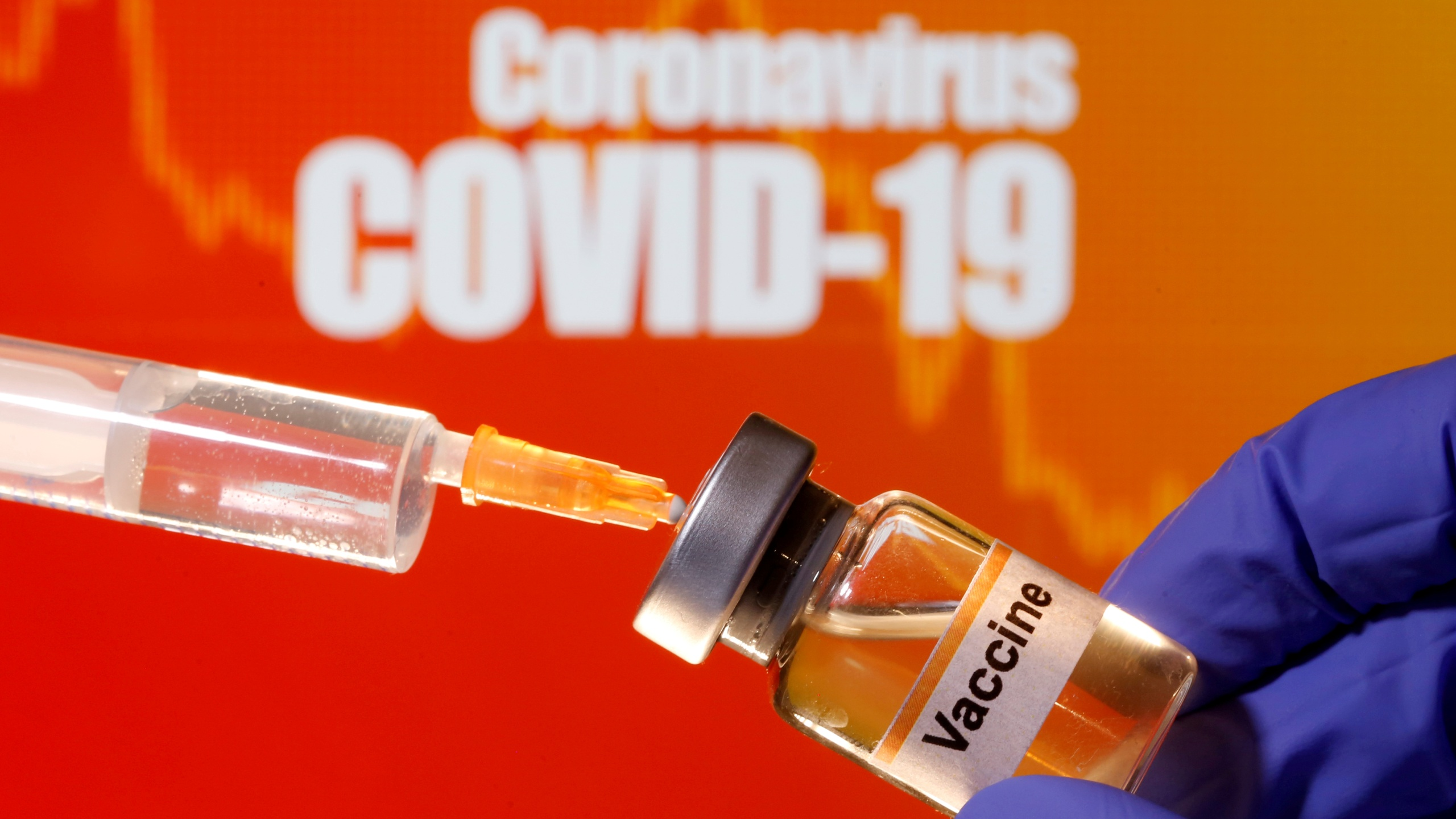 "A small bottle labeled with a ""Vaccine"" sticker is held near a medical syringe in front of displayed ""Coronavirus COVID-19"""