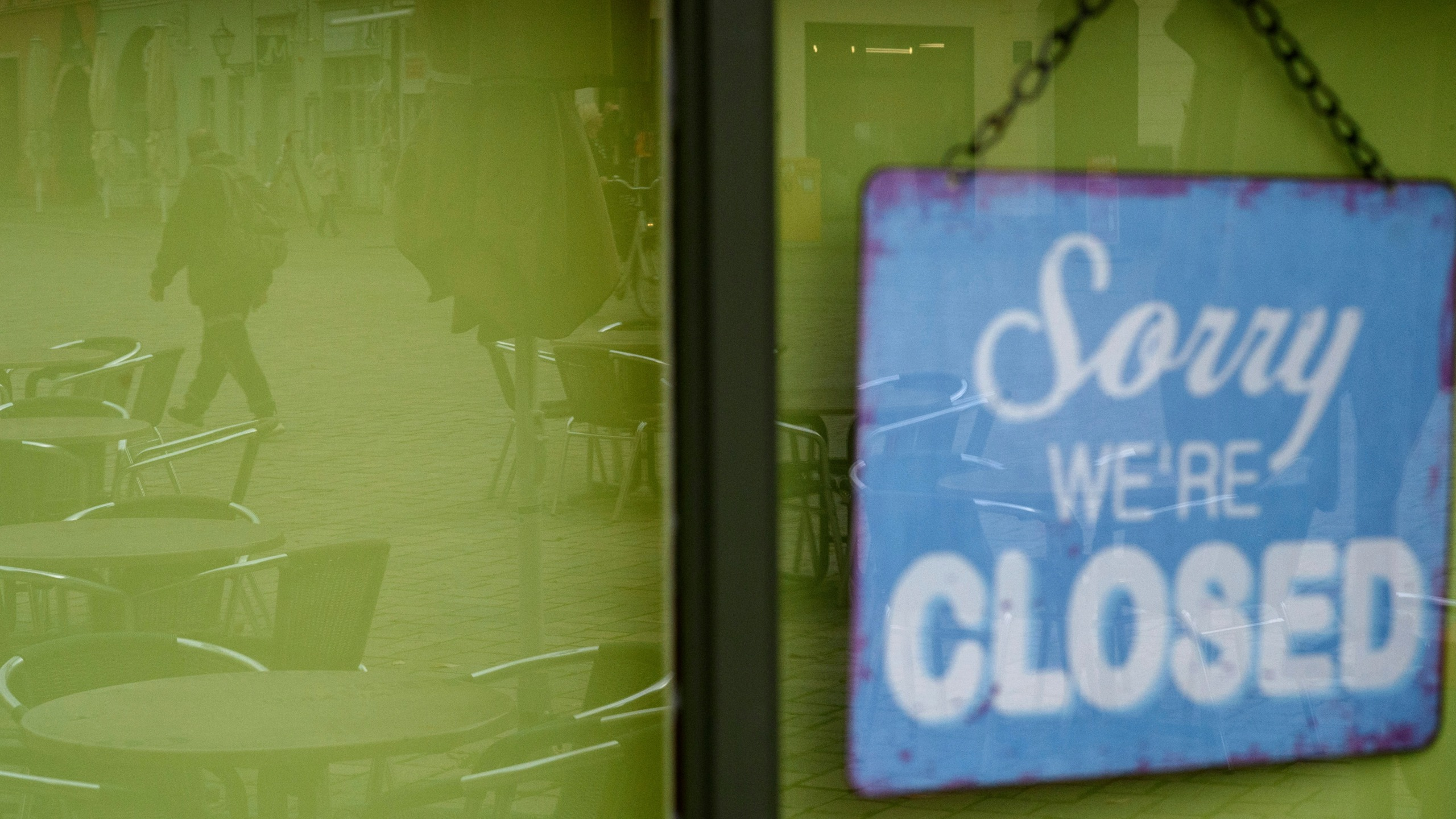 """Sorry we're closed"" is written on a sign hanging on the door of a coffee shop where the unoccupied tables and chairs are reflected in the glass pane in Germany in November 2020."
