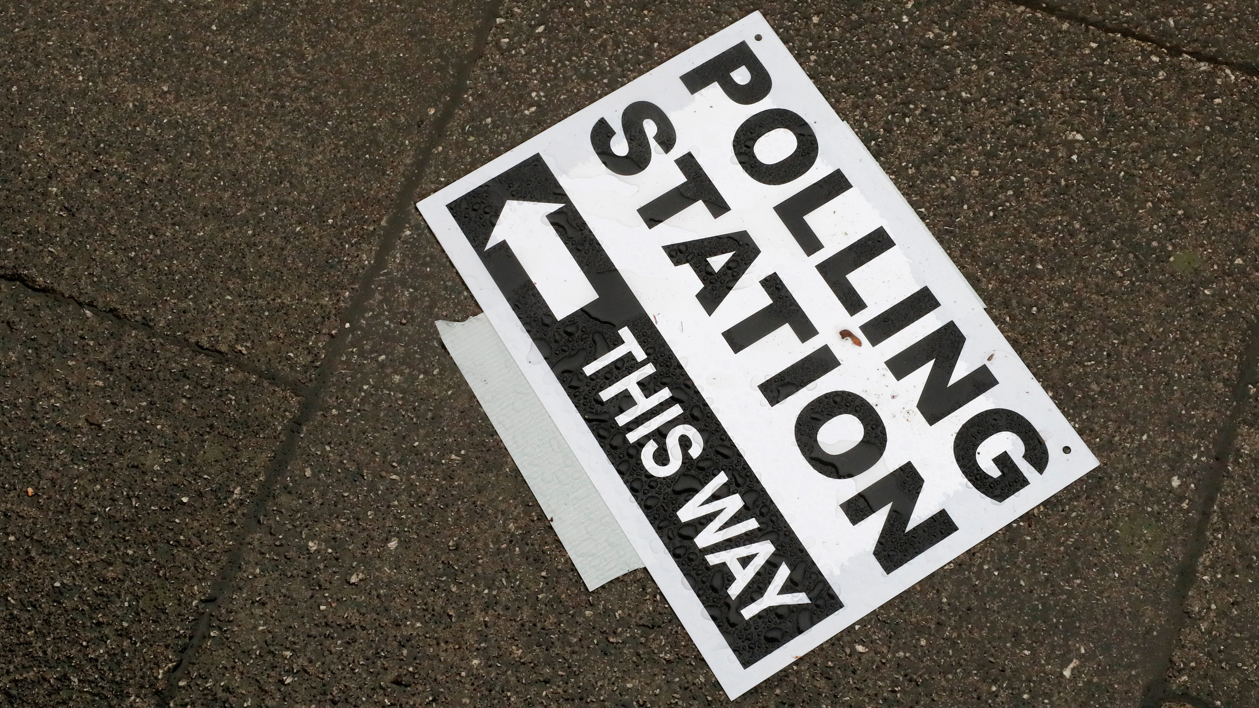 FILE - In this Thursday, Dec. 12, 2019 file photo, a polling station signpost lies on the pavement in England. (AP Photo/Frank Augstein, File)