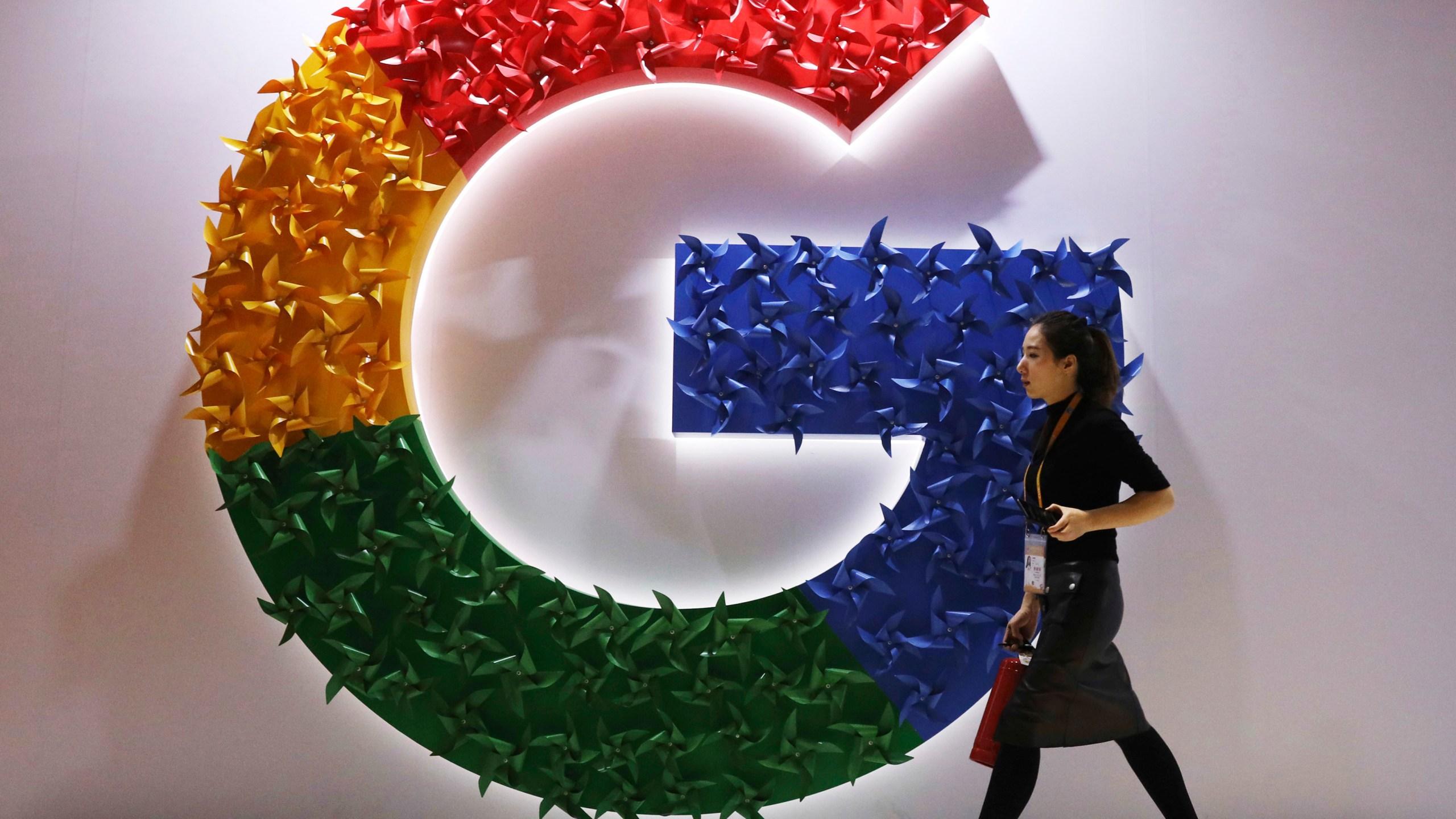 A woman walks past the logo for Google at the China International Import Expo in Shanghai. on Monday, Nov. 5, 2018. (AP Photo/Ng Han Guan, File)